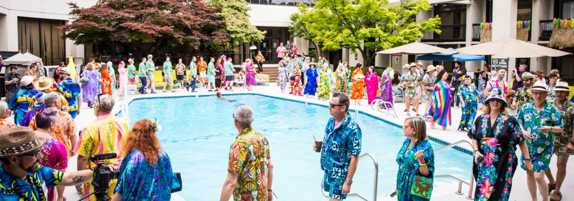 Colorfully dressed guests parade around the swimming pool at the Bananas for Cabanas and Crazy for Caftans meetup.